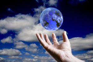 Abstract earth hovering over an open hand with sky background